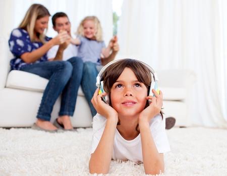 Pensive little boy listening music lying on floor photo