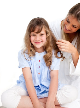long hair boy: Mother Looking At Her Daughters Hair Stock Photo