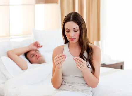 Attractive woman taking her sick husband's temperature Stock Photo - 10095798