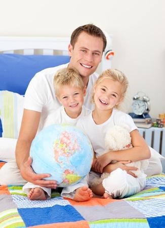 familia animada: Padre alegre y sus hijos sosteniendo un globo terretrial  Foto de archivo