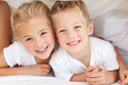 brothers: Adorable siblings playing on a bed