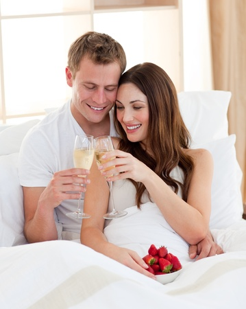 lovers in bed: Cheerful couple drinking champagne with strawberries lying in bed Stock Photo