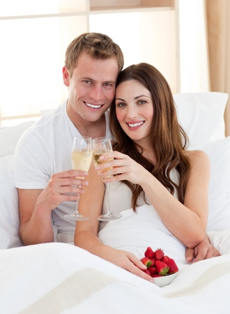 Enamoured couple drinking champagne with strawberries lying in bed Stock Photo - 10095966