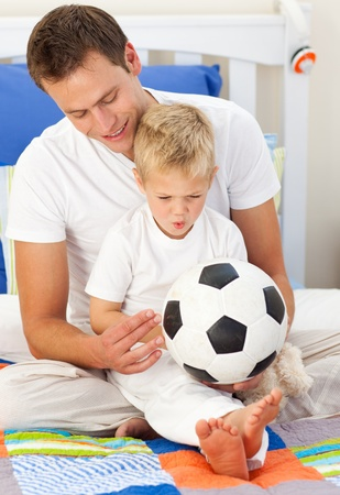 contented: Blond little boy and his father playing with a soccer ball