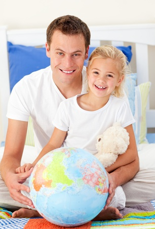 Attentive father and his daugther looking at a terrestrial globe photo
