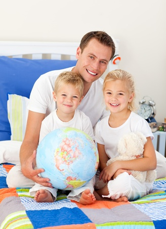 chirpy: Cute children and their father looking at a terrestrial globe