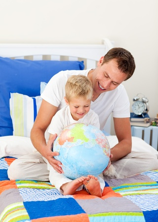 terrestrial globe: Laughing father and his son looking at a terrestrial globe