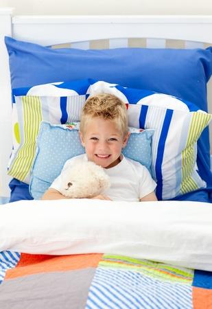 mirthful: Cute little boy lying in bed
