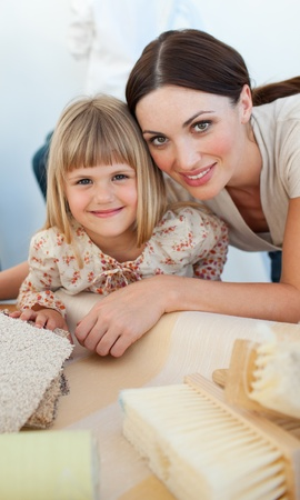 Smiling mother and her daughter decorating a room  photo