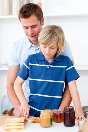 Attentive father helping his son prepare the breakfast photo