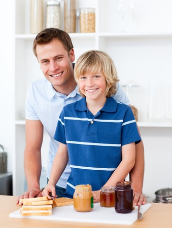 Smiling father helping his son prepare the breakfast photo