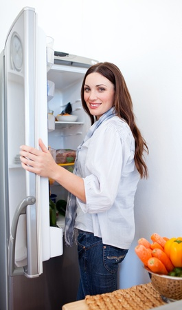 Smiling woman looking for something in the fridge photo