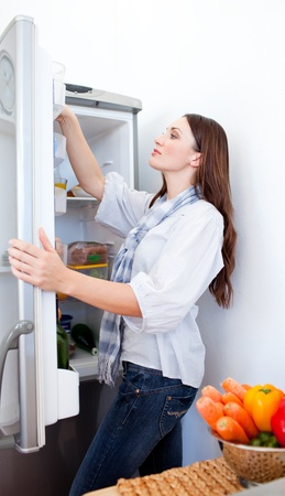 Young woman looking for something in the fridge  photo