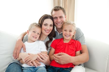 Portrait of Happy family sitting on sofa Stock Photo - 10097345