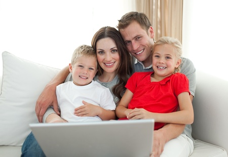 Jolly family using a computer sitting on sofa Stock Photo - 10096835
