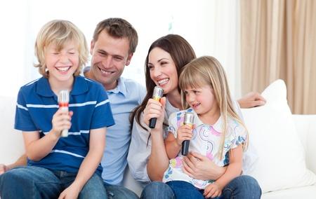 ni�o cantando: Riendo familia cantando juntos Foto de archivo