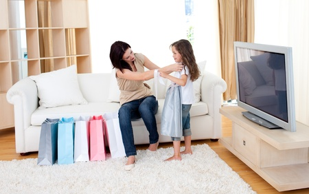 Joyful mother and her daughter at home after shopping photo