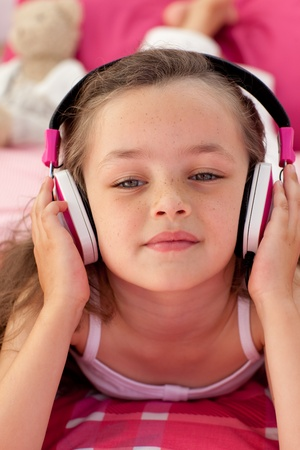 Close-up of a little girl listening musc photo