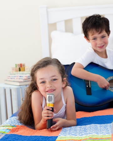 Close-up of a cute girl girl singing and her brother playing guitar Stock Photo - 10096388