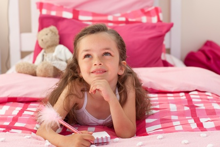 Smiling girl writing on bed photo