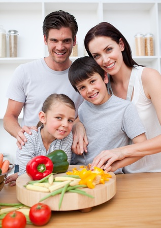 Portrait of  happy parents cooking with their children photo