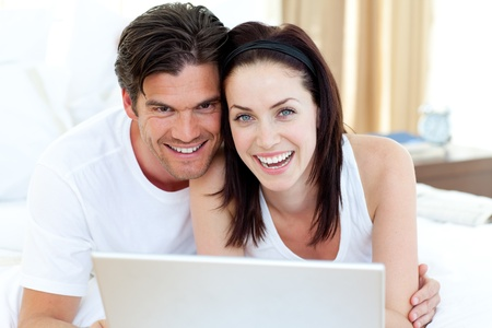Smiling couple using a laptop lying on their bed  photo