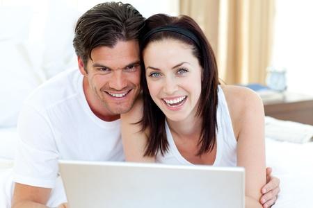 pareja en casa: Sonriente pareja utilizando un ordenador port�til acostado en su cama