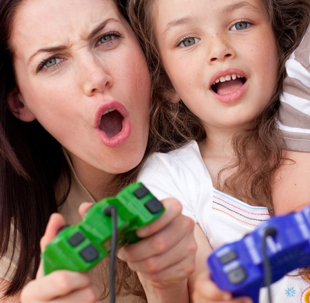 Excited mother and her daughter playing video games photo