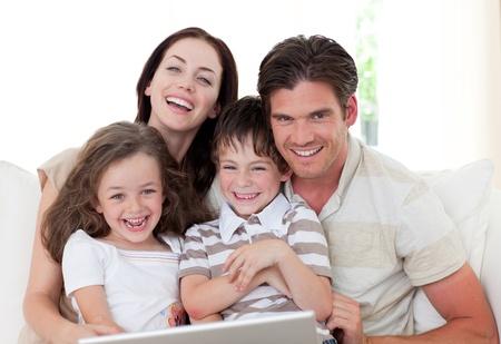 chicas comprando: Familia sonriente utilizando una computadora port�til en la sala de estar Foto de archivo
