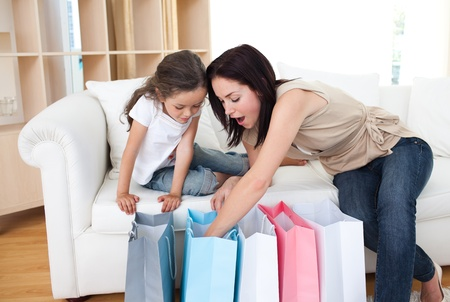 Mother and daughter unpacking shopping bags  photo
