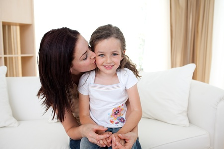 Attentive mother kissing her little girl photo