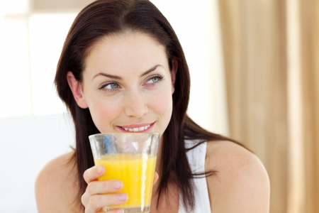 orange juice glass: Attractive woman drinking orange juice  Stock Photo