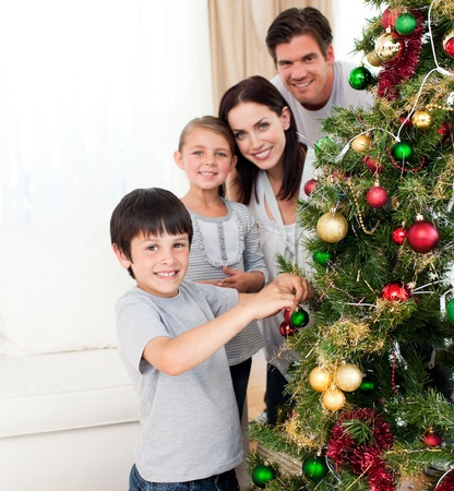 Smiling family decorating a Christmas tree photo