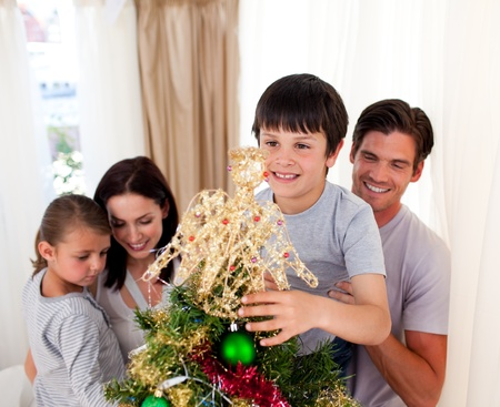 Smiling family decorating a Christmas tree at home photo