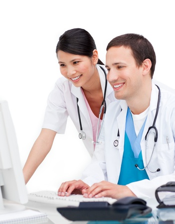 Delighted doctor and nurse working at computer photo