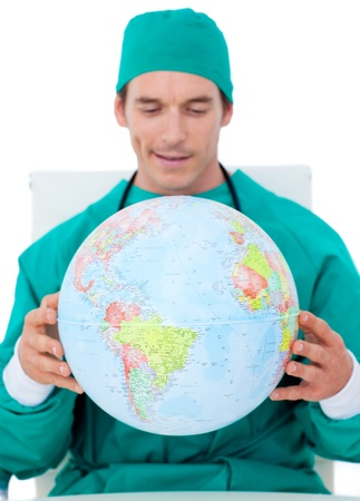 Charming doctor holding terrestrial globe photo