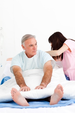 Female nurse adjusting pillows for a senior patient in a hospital  Stock Photo