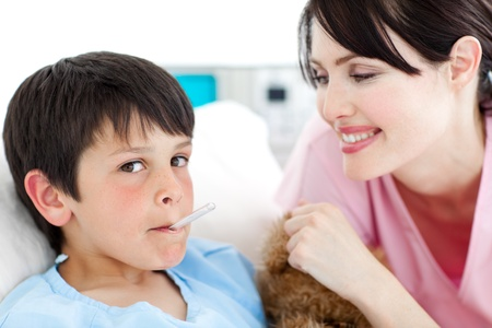 Charming nurse taking little boy's temperature  Stock Photo - 10097144