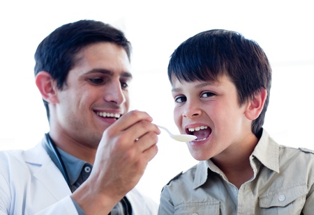 Assertive doctor giving medicine to a little boy Stock Photo - 10096399