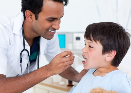 Charismatic doctor giving medicine to a little boy photo