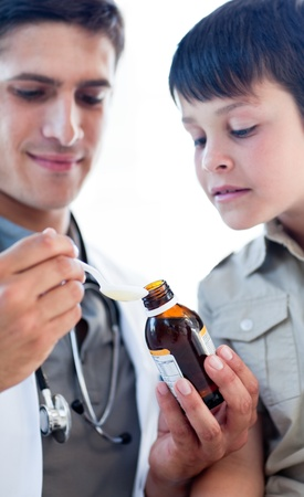 Assertive doctor giving medicine to a little boy photo