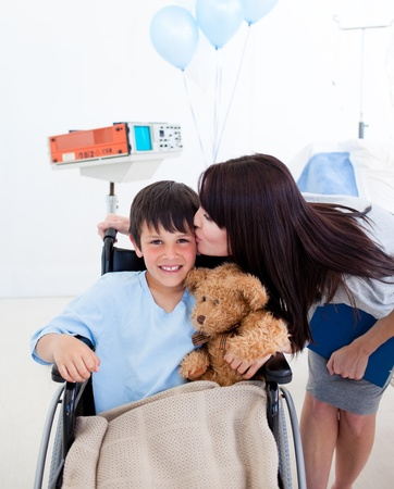 Cheerful little boy sitting on wheelchair and his mother photo