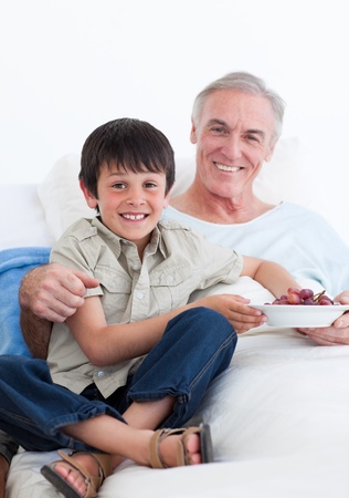 more mature: Cute little boy taking care of his grandfather