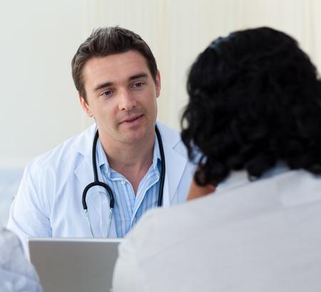 medico con paciente: Doctor masculino explicando el diagn�stico de un paciente Foto de archivo