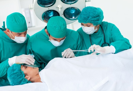 Surgeons near patient lying on an operating table photo
