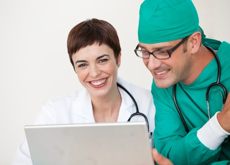 Doctor and surgeon looking at a laptop photo