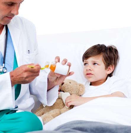 Adorable little boy taking cough medicine  photo