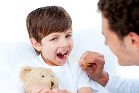 Young doctor taking little boy's temperature Stock Photo - 10106953