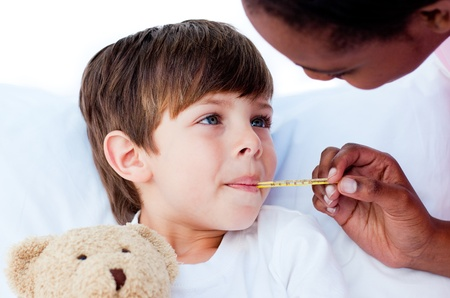 Close-up of a doctor taking childs temperature  photo