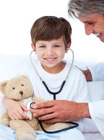 Adorable Little boy playing with his doctor  photo